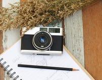 Seleccione la cámara vieja del vintage del foco en el libro y con un lápiz, flor en el de madera Foto de archivo