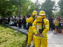 Select focus of back Firefighters in yellow suit with an oxygen tank in the back. Firefighters are teaching office workers to esca. Pe from high-rise buildings stock photography