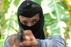Select focus of crime eyes. Robber in black ski mask aims with gun.  royalty free stock photos