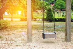 Select focus, Empty wooden swing in playground with lens flare effect. Select focus Empty wooden swing in playground with lens flare effect Royalty Free Stock Images