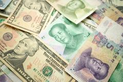 Select focus of 10 US dollar stack under China yuan banknote. Concept of Trade war between the United States and China.  royalty free stock photography