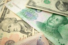 Select focus of 10 US dollar stack under China yuan banknote. Concept of Trade war between the United States and China.  stock images