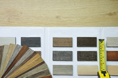 Select the sample of wood texture laminate and vinyl from catal. Variety of wood Samples of laminate and vinyl floor tile on wooden Background and catalog stock photos