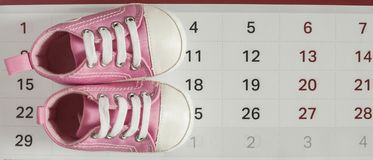 Little baby shoes with calendar. Selected due date in the calendar and detail of baby shoes Royalty Free Stock Photos