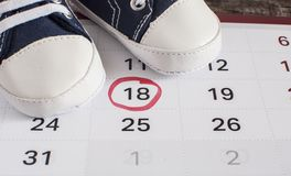 Little baby shoes with calendar. Selected due date in the calendar and detail of baby shoes Stock Photos