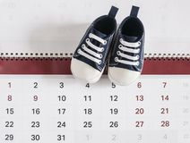Little baby shoes with calendar. Selected due date in the calendar and detail of baby shoes Royalty Free Stock Images