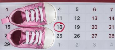 Little baby shoes with calendar. Selected due date in the calendar and detail of baby shoes Stock Image