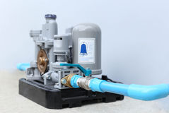 Selected focus automatic water pump with blue pipeline isolated Royalty Free Stock Photo