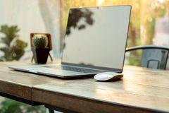 Selected focus computer mouse and laptop on wooden table in blur background. Selected focus computer mouse and laptop on wooden table in blur background stock image