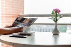 Cup of coffee and cell phone with businessman reading a newspaper with flower on the table stock images