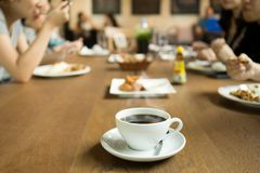 Selected focus cup of coffee with family dinner time. On the table Stock Image