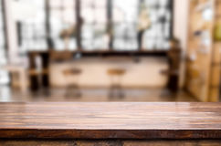Selected focus empty brown wooden table and Coffee shop blur bac Stock Images