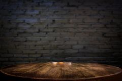 Selected focus empty brown wooden table and wall texture or old. Black brick wall blur background image. for your photomontage or product display Stock Photography