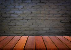 Selected focus empty brown wooden table and wall texture or old. Black brick wall blur background image. for your photomontage or product display Royalty Free Stock Photo