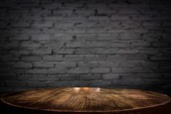 Selected focus empty brown wooden table and wall texture or old. Black brick wall blur background image. for your photomontage or product display Royalty Free Stock Photography