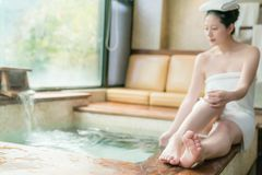 Selected focus on foot leg of young Japanese girl. Sitting on poolside with body cover towel and using hand touch the hot springs in the winter stock photo