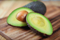 Selected focus half cut ripe avocado with seed on board Stock Photography