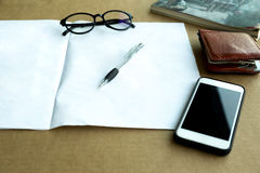 Selected focus pen and wallet , glasses and cell phone with manu. Al book on the table Stock Image