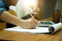 Selected focus on pencil songwriter working on new composition w. Ith laptop on the table sunlight flare royalty free stock photography