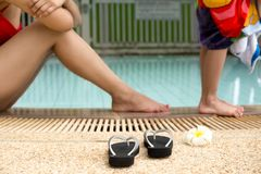 Selected focus sandal and flower on the edge of the pool with mo. Ther and little boy in background Stock Images