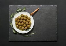 Selected olives in a white plate decorated with natural olive tree branches on a dark background. Royalty Free Stock Photo