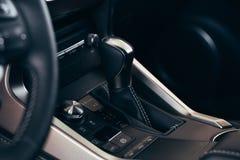 Selecteurs automatische transmissie met geperforeerd leer binnen een moderne dure auto De achtergrond is vaag stock foto's