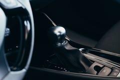 Selecteurs automatische transmissie met geperforeerd leer binnen een moderne dure auto De achtergrond is vaag stock afbeelding
