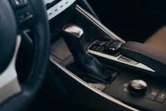 Selecteurs automatische transmissie met geperforeerd leer binnen een moderne dure auto De achtergrond is vaag stock afbeeldingen