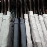 Selectie van de t-shirts die van witte en grijze mensen op hangers hangen stock foto's