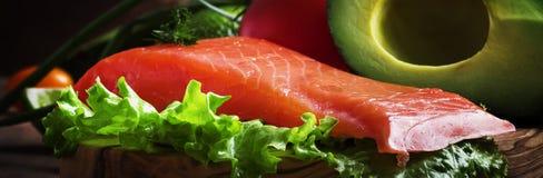 Selectie van gezonde voedsel en vetten: zalm, avocado, tomaten, sla, olijfolie, uien en kruiden, oude houten keukenlijst royalty-vrije stock afbeelding