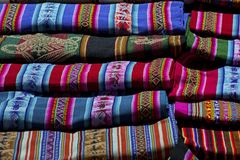 Selectie van hand geweven die kostuum en textiel voor verkoop op de lokale zondagmarkt wordt opgemaakt van Tarabuco, Bolivië stock foto