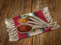 Selectie van kleurrijke kruiden in metende lepels op versleten oud Stock Fotografie