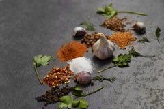 Selectie van kruiden, herbsl op zwarte steenlijst Ingredi?nten voor het koken stock foto's