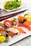 Selectie van sushiplaat met eetstokjes stock afbeelding