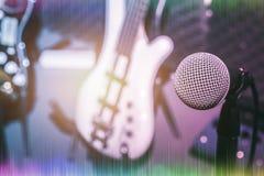 Selectieve nadruk één van microfoon met het onduidelijke beeld van elektrische baarzen en gitaar Royalty-vrije Stock Afbeelding
