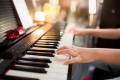 Selectieve nadruk aan de hand van het jonge geitje het spelen piano op stadium royalty-vrije stock foto's