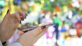 Selectieve nadruk De handen van de vrouw met smartphone in winkelcentrum Kerstmis Bezinning van zonneflarden van licht stock footage