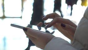 Selectieve nadruk De handen van de vrouw met smartphone in winkelcentrum Kerstmis Bezinning van zonneflarden van licht stock videobeelden