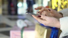 Selectieve nadruk De handen van de vrouw met smartphone in winkelcentrum Kerstmis Bezinning van zonneflarden van licht stock video