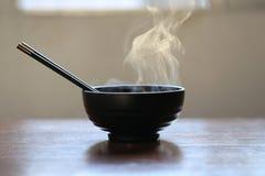 Selectieve nadruk die van rook met hete soep van onmiddellijke noedels in kom en eetstokjes op donkere achtergrond toenemen royalty-vrije stock afbeeldingen