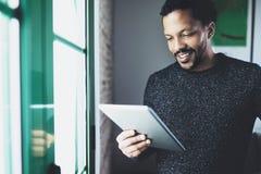 Selectieve nadruk Het glimlachen van het gebaarde Afrikaanse boek van de mensenlezing op digitale tablet terwijl status dichtbij  Royalty-vrije Stock Fotografie