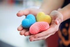 Selectieve nadruk kleurrijke veelkleurige breiende die harten door beide handen van het wijfje worden gehouden, die helpend hande royalty-vrije stock afbeelding