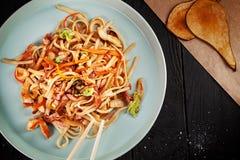 Selectieve nadruk op Chinese noedels met kip en groenten op donkere achtergrond stock afbeeldingen
