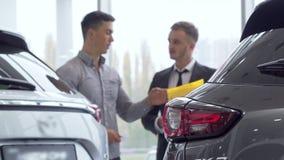 Selectieve nadruk op een auto, mannelijke klant die aan autohandelaar op de achtergrond spreken stock video
