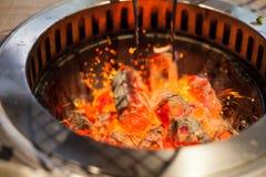 Selectieve nadruk op Gloeiend en Vlammend heet natuurlijk houten houtskoolstuk op BBQ van het voedselrestaurant de achtergrond va royalty-vrije stock afbeelding