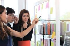 Selectieve nadruk op handen van jonge Aziatische bedrijfsmensen die strategieën op tik in conferentieruimte verklaren stock afbeelding