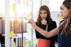 Selectieve nadruk op handen van jonge Aziatische bedrijfsmensen die strategieën op tik in conferentieruimte verklaren met zonnesc stock afbeelding