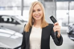 Selectieve nadruk van autosleutels in handen van verkoper in autosalon stock afbeeldingen