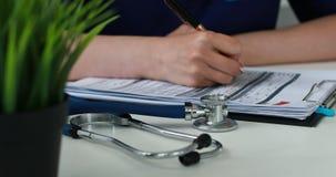 Selectieve nadruk van bloem in pot en Bebouwd beeld van stethoscoop en artsen het vullen documenten stock video