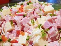 Selectieve nadruk van de salade van de hamworst met tomaat, ui, zonnebloemzaailingen en mayonaise op plaat in restaurant royalty-vrije stock afbeeldingen